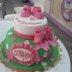 Torta di battesimo a due piani decorata con scarpine di pasta di zucchero e fiocco rosa