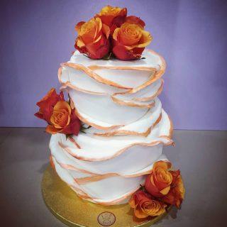 torta fiorita di nozze bianca e rossa con decorazioni eleganti e rose